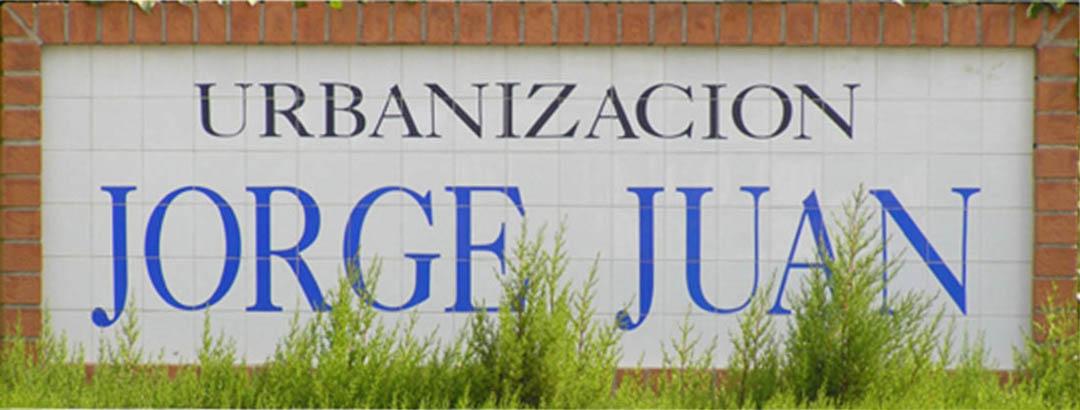 Letrero sobre azulejos para Urbanización. Tiene unas dimensiones de 285 por 90 cm de alto y en su parte superior en color azul muy oscuro pone urbanización y en su parte inferior con azul mas claro el nombre de la misma.
