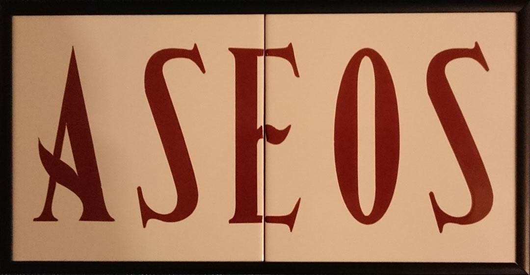 Señal sobre dos azulejos, con texto aseos con las letras marrones