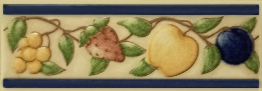 Cenefa cerámica de frutas realizada con colores muy suaves y que tanto arriba como abajo va rematada con una raya azul.