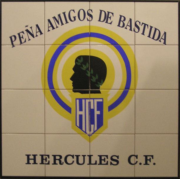 Letrero en cerámica para peña del Hércules club de fútbol que incorpora el escudo del club y alrededor de este hay leyenda alegórica al equipo y el nombre de peña