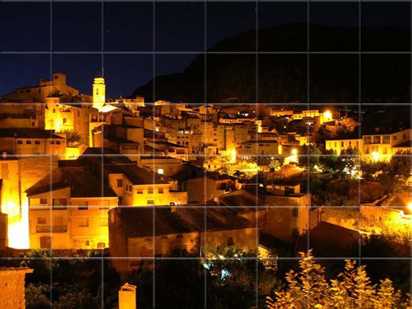 Mural cerámico de un pueblo nocturno, donde se ve desde lo alto, un pueblo en la ladera de una montaña con sus callejuelas iluminadas.