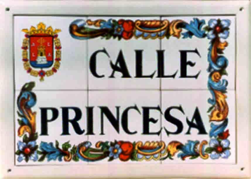 Rótulo de calle en cerámica con orla floreada y escudo de la localidad
