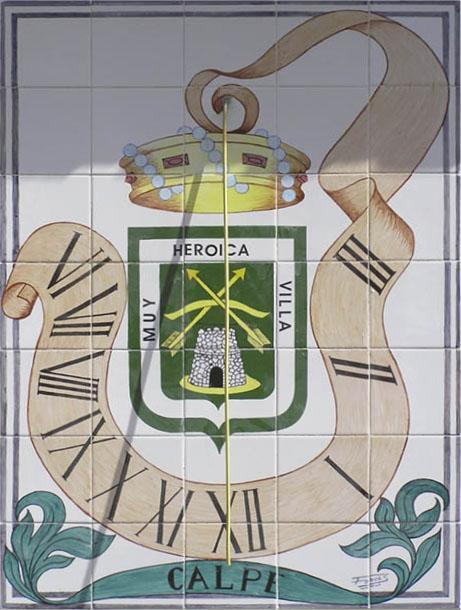 Reloj de sol en cerámica villa de Calpe. La parte central es el escudo de la villa y de su parte superior sale una cinta que a modo de estar a merced del viento se contonea para incorporar los números de las horas.