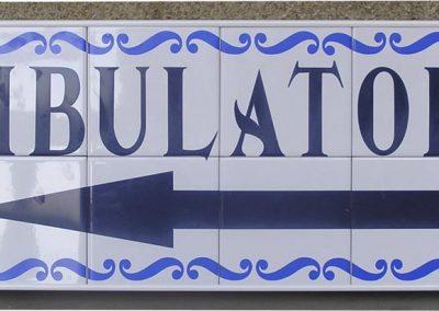 Señal en azulejos indicadora de ambulatorio con flecha