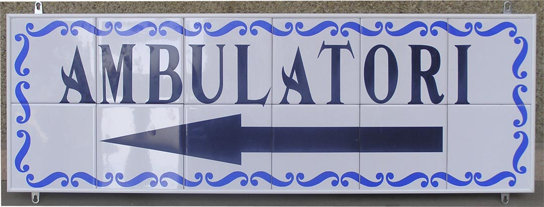 Señal en azulejos indicadora de ambulatorio con adorno de una orla y con flecha indicadora